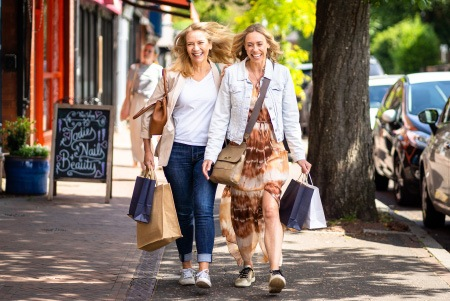 Two ladies walking with shopping bags laughing