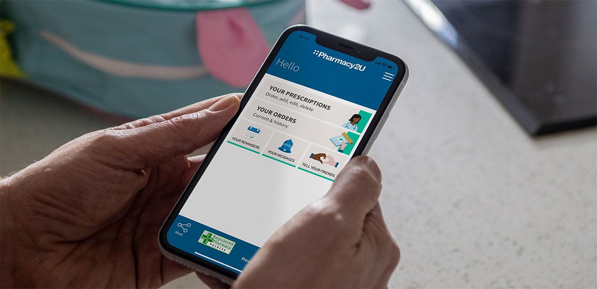 Person holding phone with pharmacy2u app on screen
