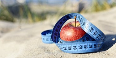 Apple on sand with measuring tape