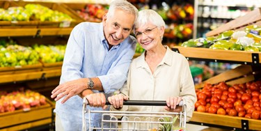 Older Couple Shopping Together In The Fruit And Veg Aisle Of A Supermarket