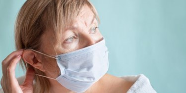 Woman wearing facemask suffering with anxiety