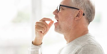 Man taking pill wearing glasses and holding glass of water