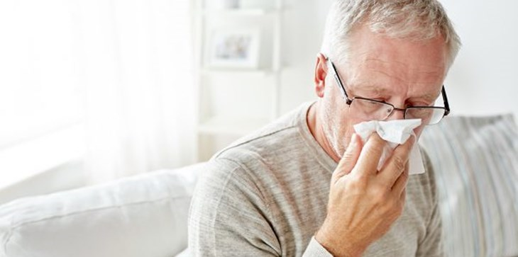 Man in living room holding tissue over his nose