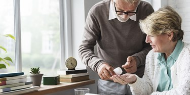 Man helping woman with medication