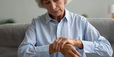 Woman holding her wrist seemingly in pain