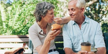 Older couple enjoying coffee and muffins on a bench outside