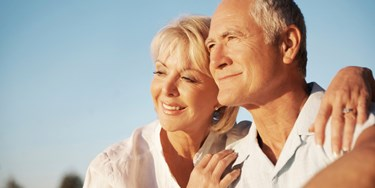 Older couple smiling and looking into the distance with a warm evening sun on their faces