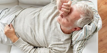 Man with migraine laid on sofa holding his head