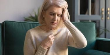Woman holding head looking unwell