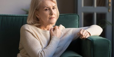 Woman on sofa looking concerned